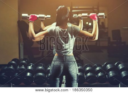 Slim bodybuilder girl lifts heavy dumbbell standing in front of the mirror while training in the gym. Sports concept fat burning and a healthy lifestyle.