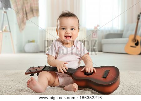 Cute little baby with guitar at home