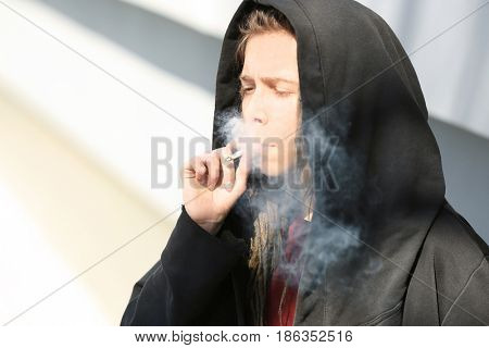 Young boy smoking weed on light background