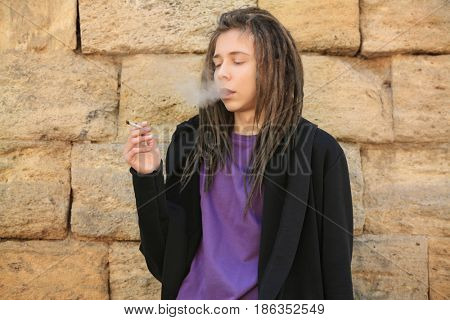 Young boy smoking weed on stone wall background