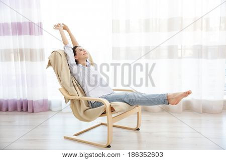 Young woman sitting on modern chair and stretching herself in light room
