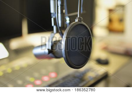 Close-up of a microphone in front of the sound mixer and computers in broadcasting radio studio. Radio station studio.