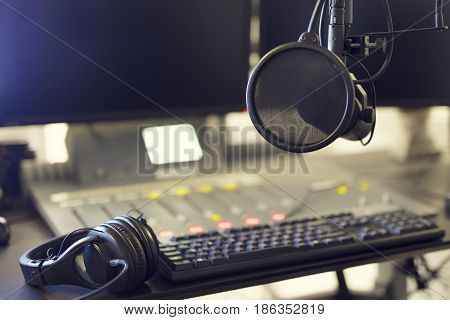 Close-up of a microphone in front of a sound mixer, headset and computers in broadcasting radio studio. Radio station studio.
