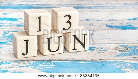 June 13th. Wooden cubes with date of 13 June on old blue wooden background.