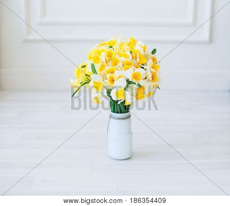 Narcissus Flowers Bouquet In A Vase On Natural Wooden Background.
