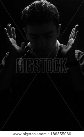 Black and white portrait of an attractive guy with his eyes closed and his hands near his face. face in the shadows
