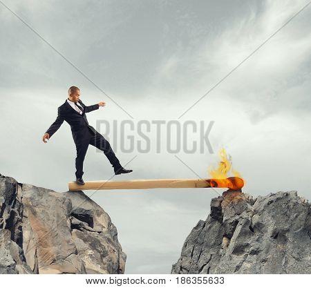 Businessman walk over a match lit between two mountains