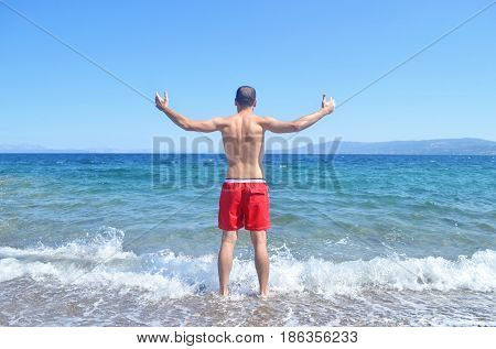 man with open hands in front of the Aegean sea Cyclades Greece