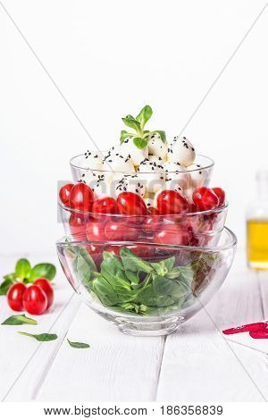 Green salad, cherry tomatoes, mini mozzarella, olive oil. Organic food on a white wooden background. Free space for your text.