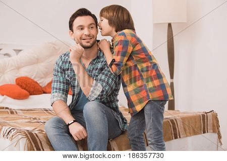 Father and son family time together at home telling secret