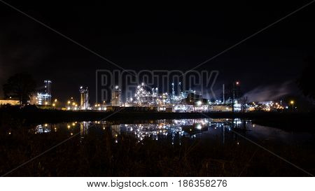 Lights of petrochemical refinery at night reflecting in the water of the pond in front of the plant. Tessenderlo Flanders Belgium Europe