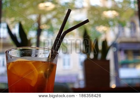 A transparent glass with a cocktail and two straws on a blurry background. In a cocktail there is a slice of lemon. Concept: rest, cold drinks, travel