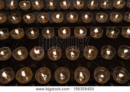 Lot of burning candles in church dark background. Sacred light. The Concept of Religion. Many lighted candles in candlesticks on black. Bright yellow light in the evening close-up