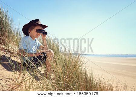Boy exploring looking through binoculars in sand dunes at the beach