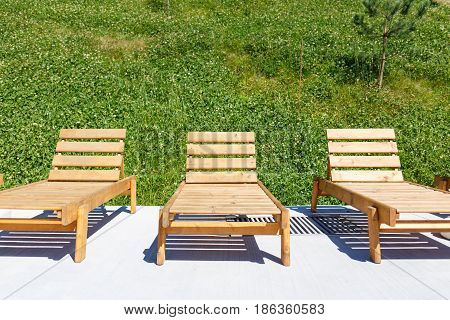 Three empty wooden chaise lounges situated on concrete floor near grassy hill. Summer mounting vacation background