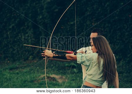 Cute Girl And Handsome Man Shooting With Bow And Arrow