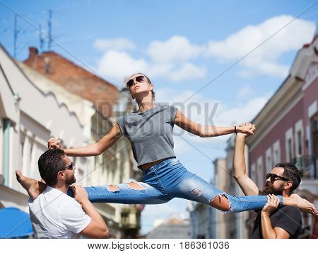 fit model in stylish sunglasses and blue jeans sitting leg split on shoulders of two bearded handsome men on sunny summer day on city street. Active lifestyle friends
