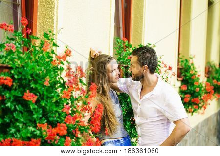 man in white shirt looking at smiling cute girl or adorable woman with long hair near blossoming flowers floral street decoration on sunny summer day. Couple in love. Dating relationship