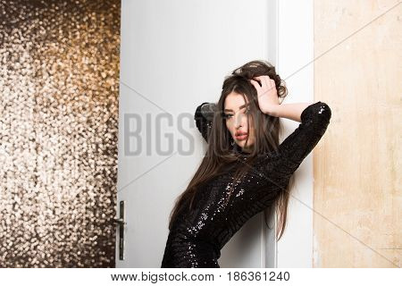 Pretty Fashion Girl In Sequin Dress Leaning On White Door