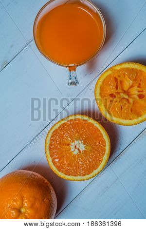A glass of fresh orange juice with sliced oranges on a wooden table. The preparation of fresh orange juice is primordial to product advertising