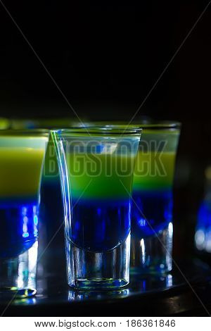 Shot cocktails. Blue and yellow layered cocktails or shooters in shot glasses mixed alcoholic drinks served on countertop in bar or night club on dark background. Entertainment and lifestyle