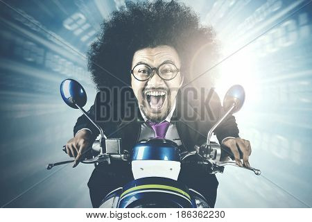 Picture of Afro businessman riding a scooter while racing in competition with fast motion blur