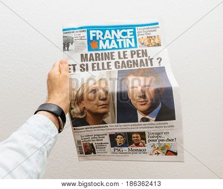 PARIS FRANCE - MAY 10 2017: Man holding France Matin newspaper front page against white background with the picture of the newly elected French president Emmanuel Macron and Marine Le Pen