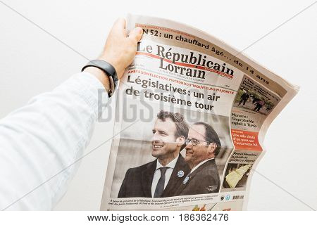 PARIS FRANCE - MAY 10 2017: Man holding le republicain lorrain newspaper front page against white background with the picture of the newly elected French president Emmanuel Macron the 8th President of France