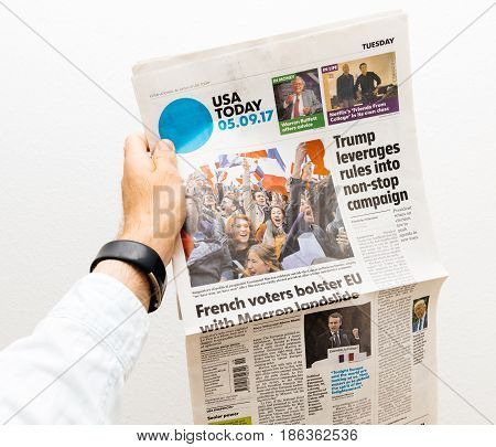 PARIS FRANCE - MAY 10 2017: Man holding USA today newspaper front page against white background with the picture of the newly elected French president Emmanuel Macron the 8th President of France