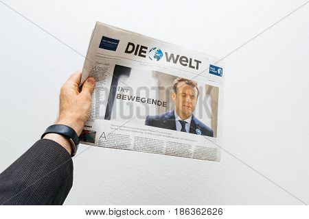 PARIS FRANCE - MAY 10 2017: Man holding Die Welt newspaper front page against white background with the picture of the newly elected French president Emmanuel Macron the 8th President of France