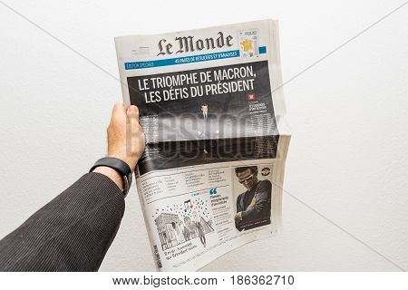 PARIS FRANCE - MAY 10 2017: Man holding Le Monde newspaper front page against white background with the picture of the newly elected French president Emmanuel Macron the 8th President of France