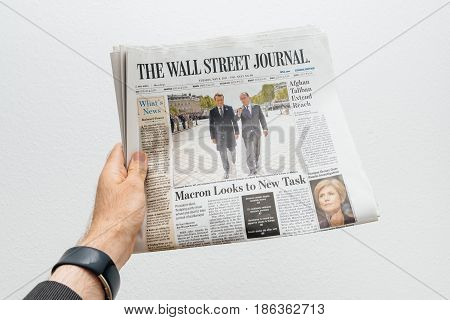 PARIS FRANCE - MAY 10 2017: Man holding The Wall Street journal newspaper front page against white background with the picture of the newly elected French president Emmanuel Macron the 8th President of France