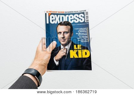 PARIS FRANCE - MAY 10 2017: Man holding L Express magazine newspaper front page against white background with the picture of the newly elected French president Emmanuel Macron the 8th President of France