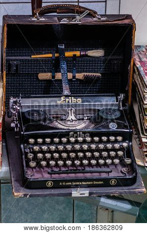 Moscow, Russia - March 19, 2017: Vintage typewriter in old shabby travel suitcase at the fair of antique collectors items