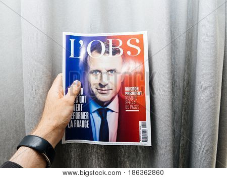 PARIS FRANCE - MAY 10 2017: Man holding L'Obs newspaper front page against gray background with the picture of the newly elected French president Emmanuel Macron the 8th President of France