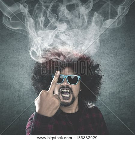 Afro man with curly hair looks angry and rude showing a middle finger with smoke coming out of his head