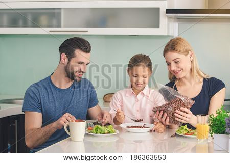 Young family sitting eating breakfast meal together in kitchen