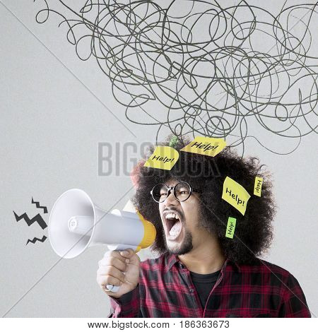 Young Afro person looks angry and shouting through a megaphone under chaotic symbol shot with help texts on his curly hair