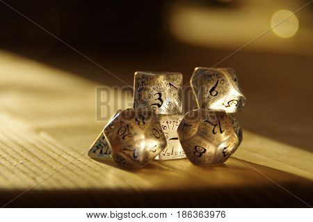 Few transparent rpg dice on table highlighted by the sun. D&D - Dungeons and dragons.