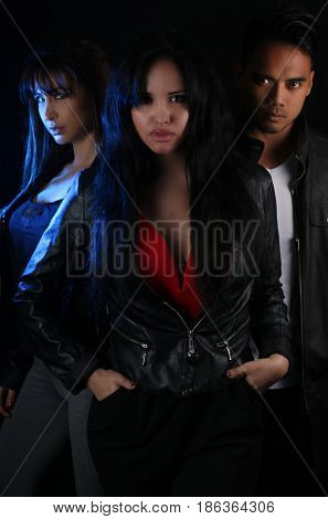 Three young vampires posing on a black background