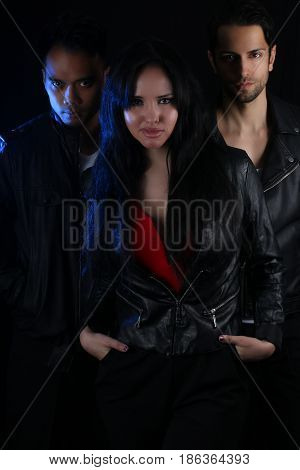 three attractive vampires over a dark background