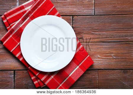 Empty Plate With Napkin On Brown Wooden Table