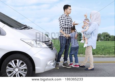 Image of Asian family arguing while standing near a car with their children on the roadside