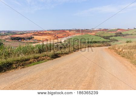 Industrial construction expanding earthworks infrastructure expansion into countryside sugarcane fields landscape.