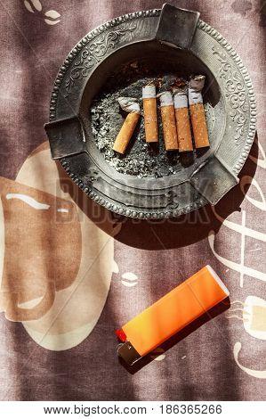 Various cigarette butts in full ashtray and orange plastic lighter on table