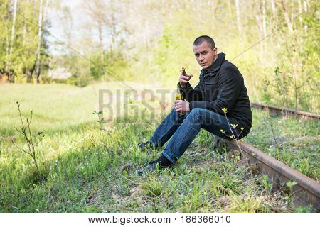 Short-cut man sits on the rails in the forest with a cigarette and a bottle in his hands