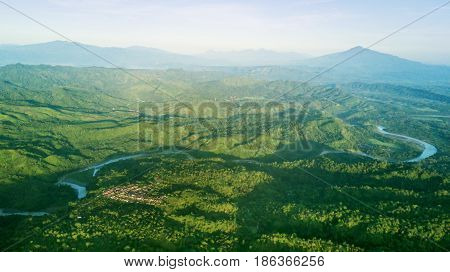 Beautiful aerial view of mountain valley with a village river and green forest. Shot at Majalengka West Java Indonesia