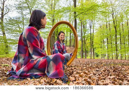 Colombian woman sitting with mirror in beech forest during spring