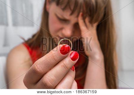 Sad woman is holding wedding ring - divorce concept