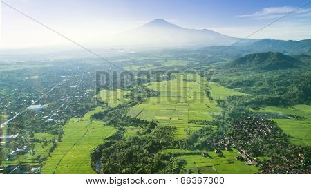 Beautiful aerial view of paddy field and village in mountain valley at misty morning Shot at Majalengka West Java Indonesia